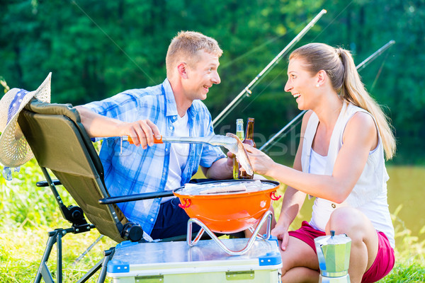 Man and woman having barbeque grilling fish  Stock photo © Kzenon