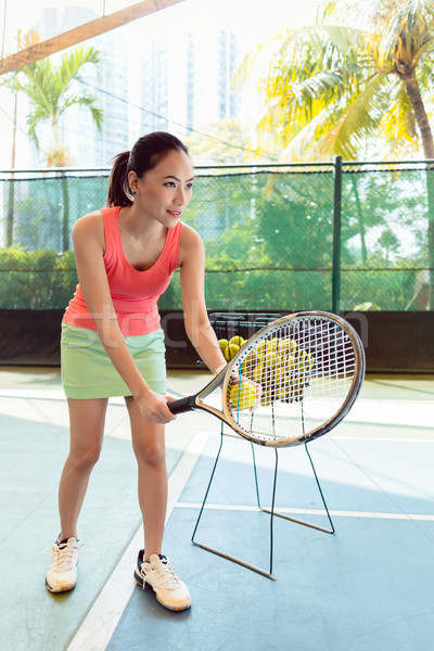 Beautiful Asian tennis player holding the racket and the ball before serving Stock photo © Kzenon