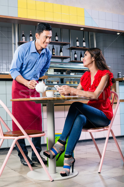Handsome waiter flirting with a beautiful woman while serving coffee Stock photo © Kzenon