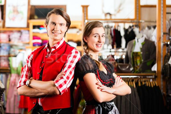 Couple is trying Dirndl or Lederhosen in a shop Stock photo © Kzenon