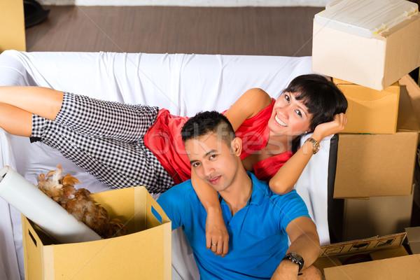 Asian couple having break while moving in Stock photo © Kzenon