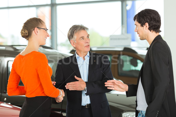 Mature man handshaking with young couple and auto in car dealership Stock photo © Kzenon