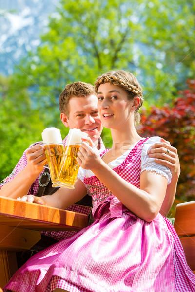 Happy Couple in Beer garden drinking beer Stock photo © Kzenon