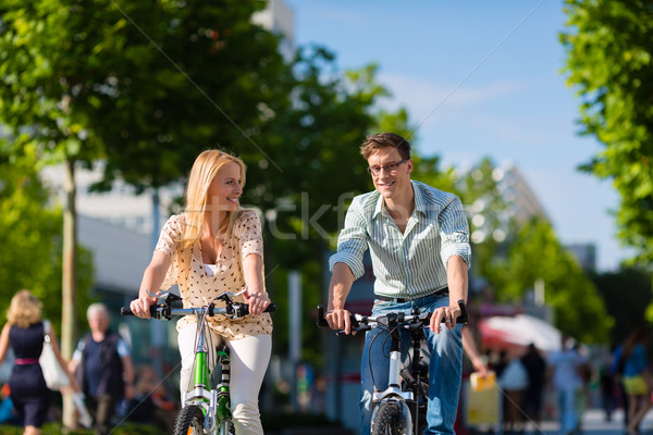Couple - man and woman - riding their bikes or bicycles in their free time and having fun on a sunny Stock photo © Kzenon