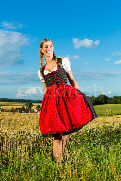 Young woman on meadow wearing dirndl Stock photo © Kzenon