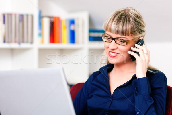 Kadın evden çalışma dizüstü bilgisayar kullanıyorsanız telefon oturma kitaplık Stok fotoğraf © Kzenon