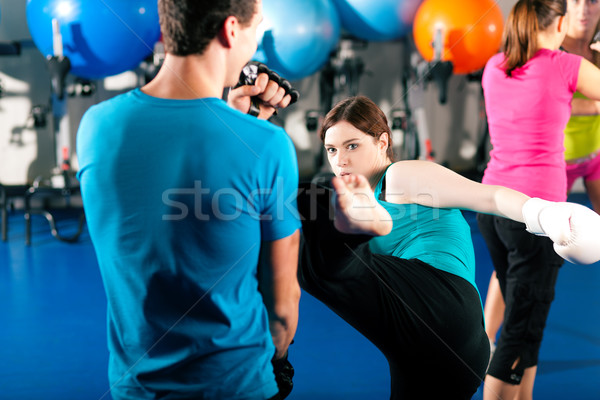 Female kick boxer with trainer in sparring Stock photo © Kzenon