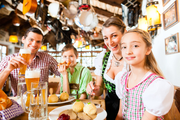 Bavarian family in German restaurant eating Stock photo © Kzenon