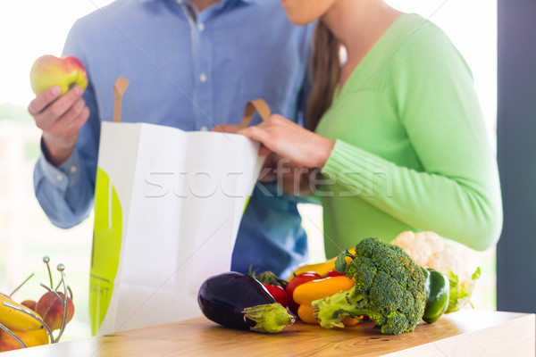 Couple unpacking grocery shopping bag at home Stock photo © Kzenon