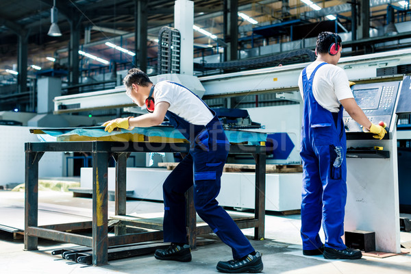 Worker team in factory discussing in front of machine Stock photo © Kzenon