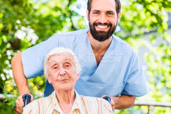 Geriatric nurse pushing senior lady in wheel chair thru home Stock photo © Kzenon