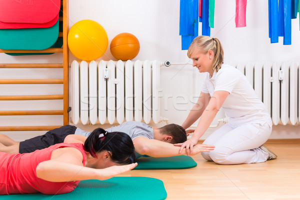 Physiotherapist giving patients gymnastic exercise Stock photo © Kzenon