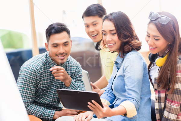 Creative team watching a surprising business presentation on tab Stock photo © Kzenon