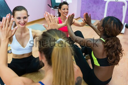 Cheerful woman clapping the hands in workout during group class  Stock photo © Kzenon