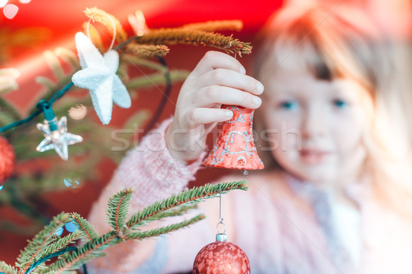 Young girl decorating the Christmas tree, holding some Christmas Stock photo © Kzenon