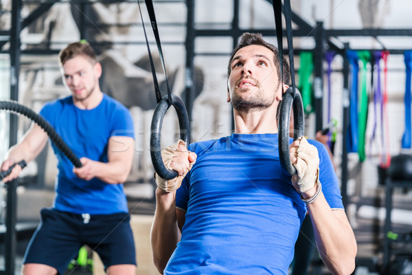 Man at rings doing fitness exercise in gym Stock photo © Kzenon