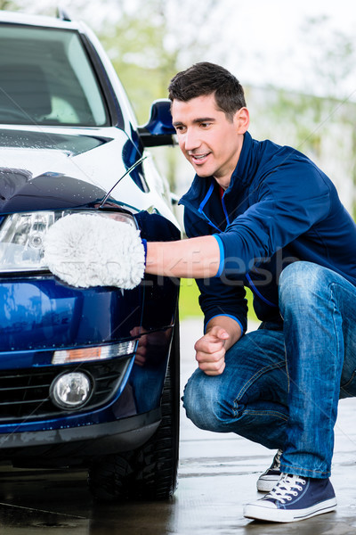 Proud car owner cleaning the headlamps Stock photo © Kzenon