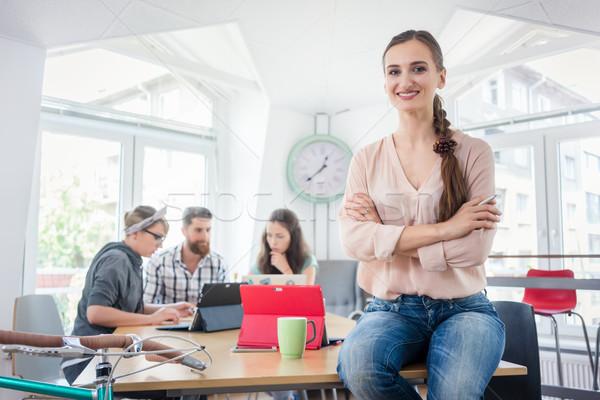 Portrait of a successful entrepreneur sitting on a desk in the office Stock photo © Kzenon