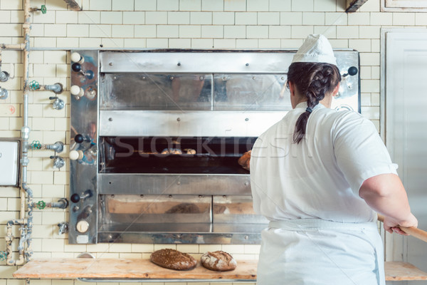 Baker getting fresh bread with shovel out of oven Stock photo © Kzenon