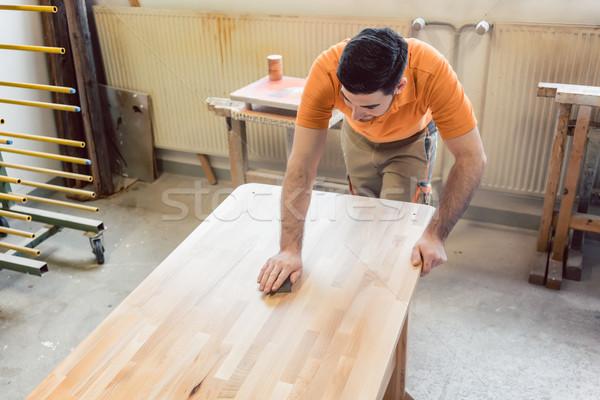 Carpenter polishing and varnishing a table Stock photo © Kzenon