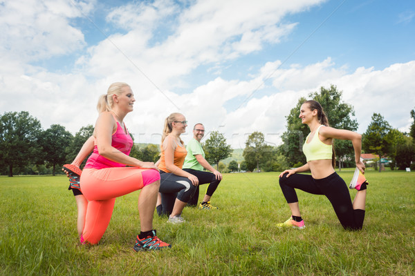 Family with fitness trainer exercising in nature with coach Stock photo © Kzenon