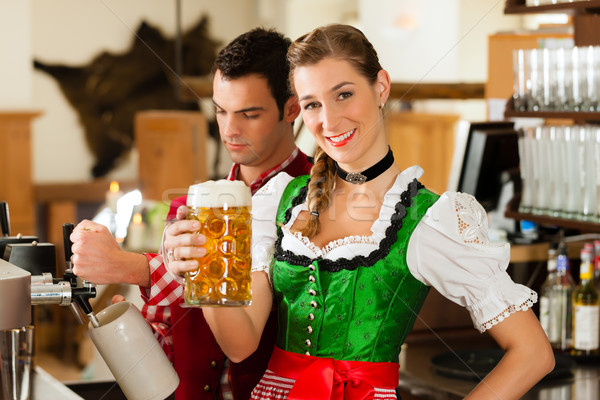 Young man drawing beer in restaurant or pub Stock photo © Kzenon
