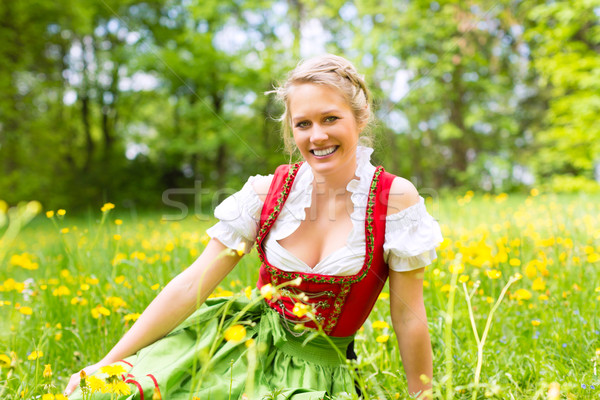 Woman in traditional Bavarian clothes or dirndl on a meadow Stock photo © Kzenon