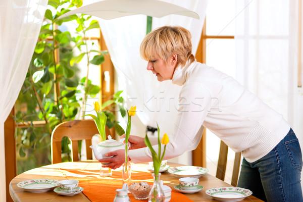 Woman setting the table for tea of coffee time Stock photo © Kzenon