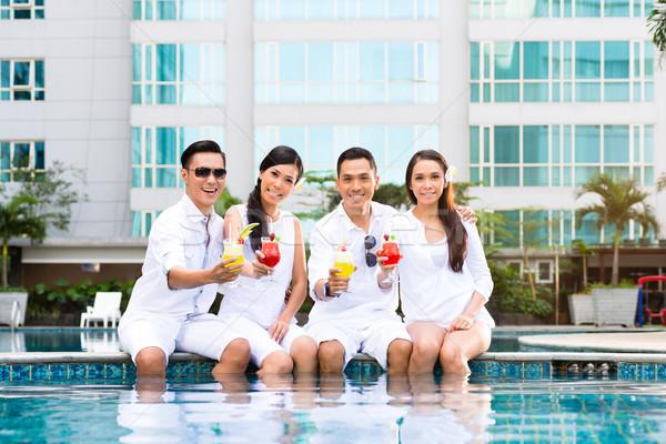 Asya arkadaşlar oturma otel yüzme havuzu kokteyller Stok fotoğraf © Kzenon