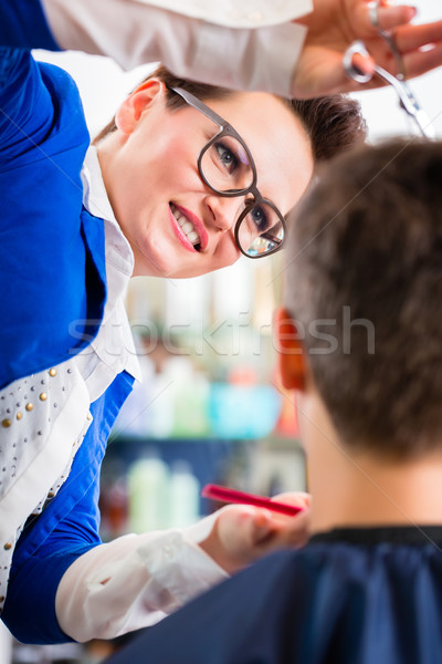Hairdresser cutting man hair in barbershop Stock photo © Kzenon