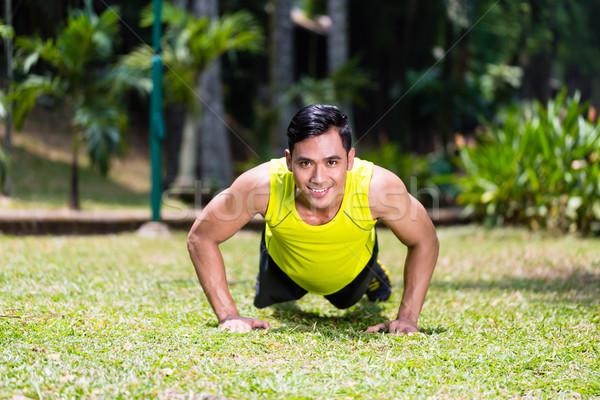 Strong Asian man doing sport push-up in park Stock photo © Kzenon