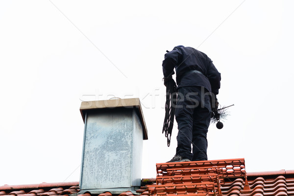 Chimney sweep on roof of home working Stock photo © Kzenon