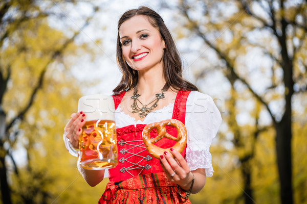 Girl wearing Dirndl with Pretzel and beer mug Stock photo © Kzenon