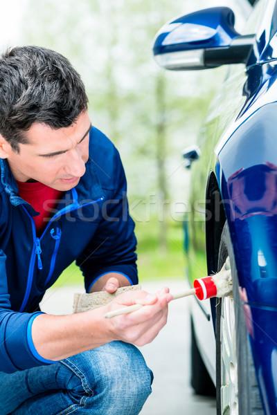 Man cleaning the alloy wheel hub of his car Stock photo © Kzenon