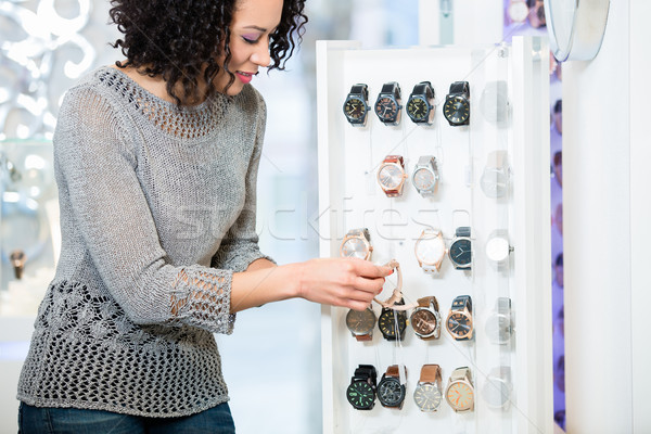 Young woman in jewellery store looking for wristwatches Stock photo © Kzenon