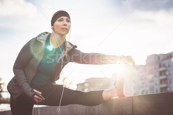 Young woman stretching her leg during outdoor warming up routine Stock photo © Kzenon