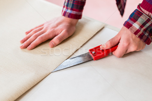 Close-up of the hands of a man cutting a new wallpaper sheet dur Stock photo © Kzenon