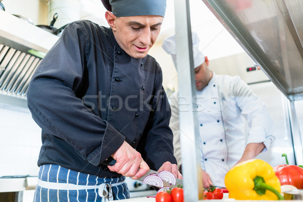 Chefs cooking and cutting vegetables and tomatoes Stock photo © Kzenon