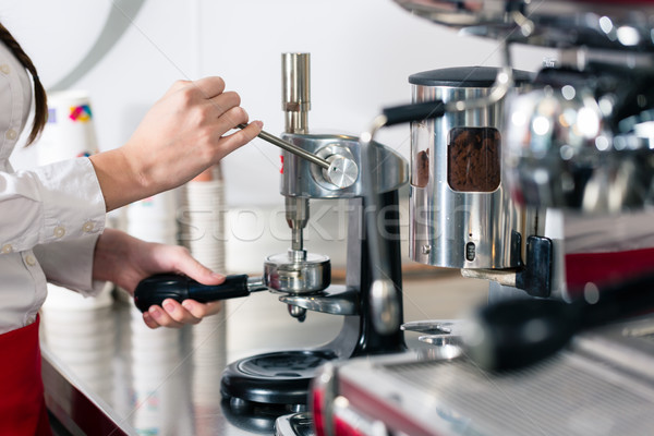 Waiter preparing espresso at an automatic coffee machine Stock photo © Kzenon