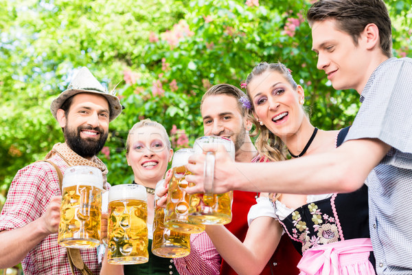 Friends standing under chestnut toasting with beer Stock photo © Kzenon