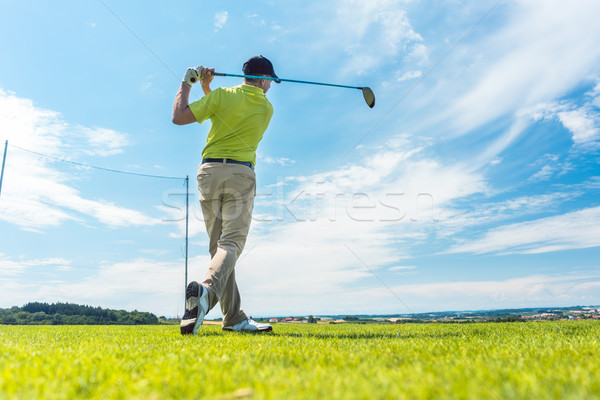 Man in the finish position of a driving swing while playing golf Stock photo © Kzenon
