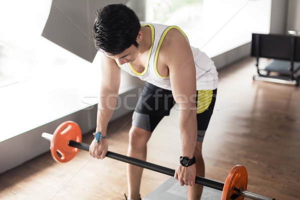 Man exercising bent over rowing with barbell for back muscles Stock photo © Kzenon