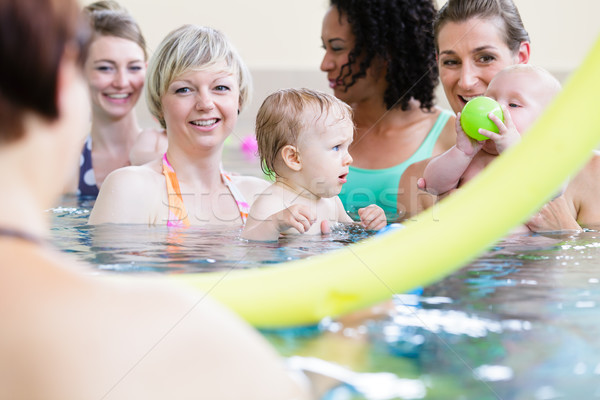 Small kids and their mothers playing with balls at baby swimming course Stock photo © Kzenon
