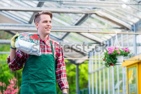 Cheerful young man carrying a bag of potting soil while working  Stock photo © Kzenon