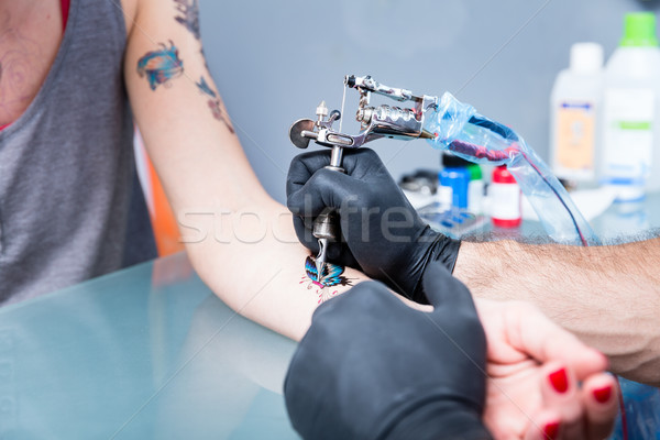 Close-up of the hands of a skilled tattoo artist wearing black gloves Stock photo © Kzenon