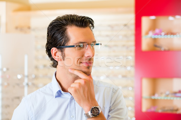 Young man at optician with glasses Stock photo © Kzenon