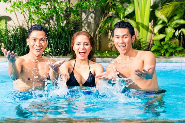 Asian friends swimming in pool Stock photo © Kzenon
