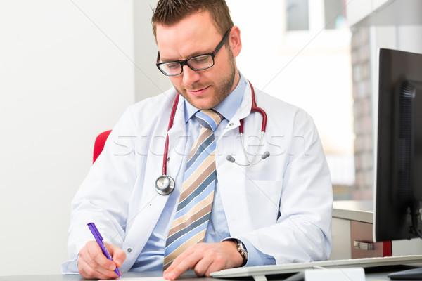 Jovem médico escrita médico prescrição cirurgia Foto stock © Kzenon