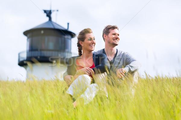 Couple enjoying holiday in front of lighthouse Stock photo © Kzenon