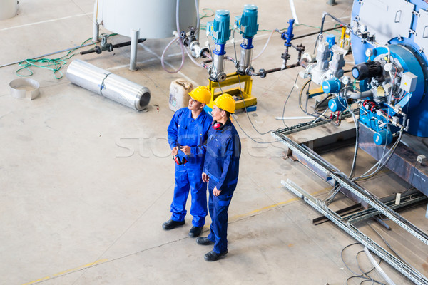 Two workers in industrial factory discussing Stock photo © Kzenon